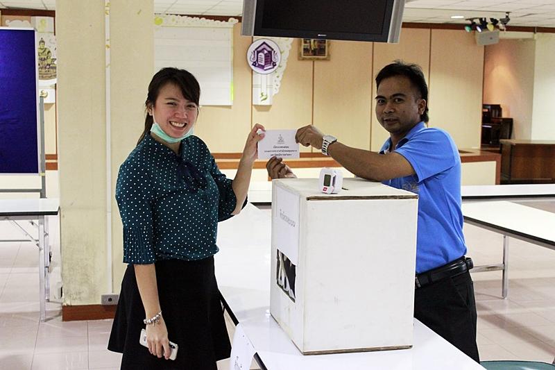 ภาพผู้ร่วมลงคะแนนสรรหาคณะกรรมการประจำสำนักหอสมุดกลางส่งบัตรลงคะแนนแก่เจ้าหน้าที่ประจำหีบบัตร