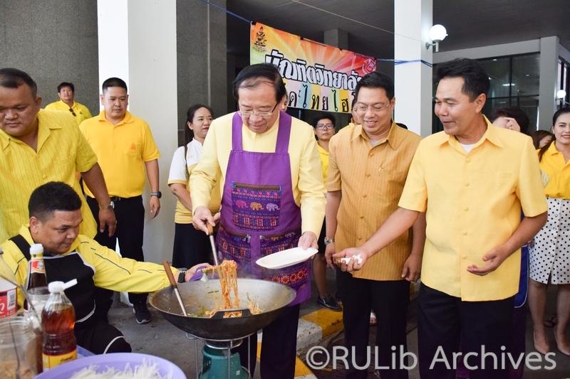 ภาพผู้ช่วยศาสตราจารย์ วุฒิศักดิ์ ลาภเจริญทรัพย์ อธิการบดีมหาวิทยาลัยรามคำแหง ประธานในพิธีเปิดโรงทานฯ  ทำผัดไทยแจกผู้ร่วมงาน  2 ธันวาคม 2562